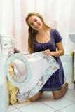 Mädchen, das clothers von der Waschmaschine nimmt Lizenzfreies Stockfoto
