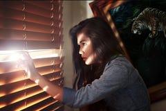 Mädchen, das in das Fenster späht Lizenzfreies Stockbild