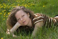Mädchen, das in das Gras legt Lizenzfreies Stockbild