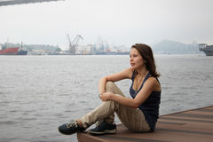 Mädchen, das das Meer betrachtend sitzt Stockbild