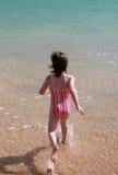 Mädchen, das in das Wasser läuft lizenzfreies stockbild