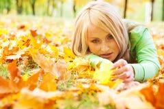 Mädchen, das in den Blättern liegt Stockfotos