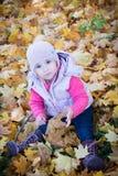 Mädchen, das in den Blättern sitzt Lizenzfreie Stockfotos