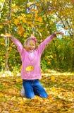 Mädchen, das in den Blättern spielt. lizenzfreie stockfotos