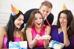Mädchen, das den Geburtstagskuchen umgeben von den Freunden an der Partei betrachtet Stockfotos