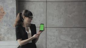 Mädchen, das in den Händen des Telefons mit einem grünen Hintergrund HD erklärt stock video footage