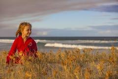Mädchen, das in den Sanddünen spielt Stockbild