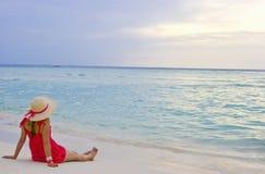 Mädchen, das den Sonnenuntergang auf dem Strand überwacht stockfotografie
