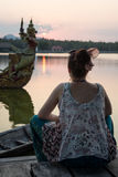Mädchen, das den Sonnenuntergang aufpasst und in Kanchanaburi, Thailan meditiert Stockbild