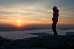 Mädchen, das den Sonnenuntergang betrachtet Stockfoto