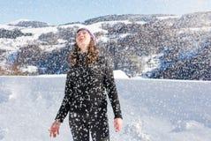 Mädchen, das in den starken Schneefällen auf dem Berg steht Stockfoto