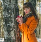 Mädchen, das in den Wald im Kaffee des Winters c geht Stockfoto