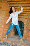 Mädchen, das an der alten Backsteinmauer steht Lizenzfreies Stockfoto