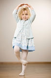 Mädchen, das in der Ballerinahaltung zu Fuß balanciert steht stockfotografie