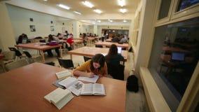 Mädchen, das in der Bibliothek studiert stock video