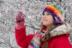 Mädchen, das in der bunten warmen Kleidung auf schneebedecktem Wald steht Stockfoto