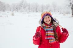 Mädchen, das in der bunten warmen Kleidung auf schneebedeckter Landschaft steht Stockfotografie
