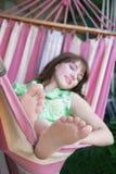 Mädchen, das in der Hängematte sich entspannt Stockfotos