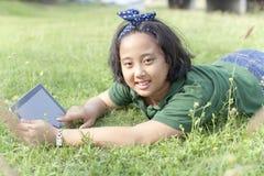 Das Mädchen, das auf grünem Gras mit Computer liegt, tablet in der Hand Lizenzfreie Stockfotos