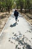 Mädchen, das in der Hopse im städtischen Garten spielt Lizenzfreie Stockfotos