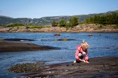 Mädchen, das an der Küstenlinie spielt Stockfotos
