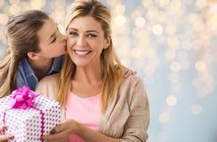 Mädchen, das der Mutter über Lichtern Geburtstagsgeschenk gibt Lizenzfreie Stockfotos