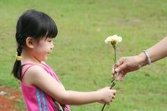 Mädchen, das der Mutter Gartennelke gibt. Lizenzfreies Stockfoto