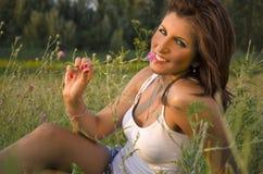 Mädchen, das in der riechenden Blume des Grases liegt lizenzfreies stockbild