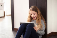 Mädchen, das an der Tablette spielt lizenzfreie stockfotos
