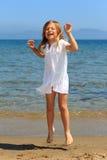 Mädchen, das in die Luft auf Strand springt Stockfotografie