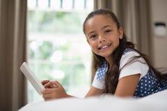 Mädchen, das digitale Tablette beim auf Bett zu Hause liegen verwendet lizenzfreies stockbild