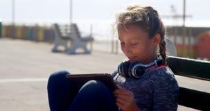 Mädchen, das digitale Tablette am Strand 4k verwendet stock footage