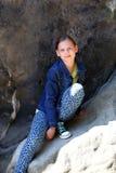 Mädchen, das draußen auf einem Felsen sitzt Stockbild