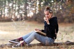 Mädchen, das draußen ein Buch liest und Tasse Kaffee hat stockfotos