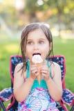 Mädchen, das draußen Eiscreme isst stockbild