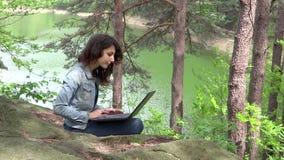 Mädchen, das draußen an Laptop arbeitet stock footage