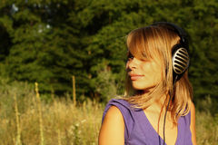 Mädchen, das draußen Musik geht und hört Stockfoto