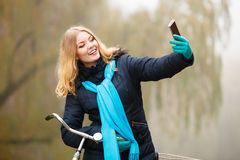 Mädchen, das draußen Selbstphoto mit Telefon macht Stockfotografie