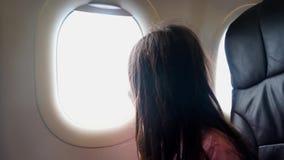Mädchen, das draußen vom Flugzeugfenster schaut stock video