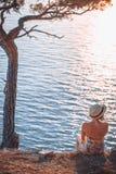 Mädchen, das durch das Meer bei Sonnenuntergang sitzt Stockfotografie