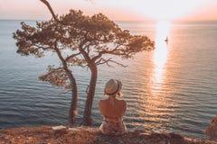 Mädchen, das durch das Meer bei Sonnenuntergang sitzt und ein überschreitenes Boot betrachtet Stockfotos