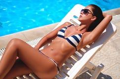 Mädchen, das durch das Pool liegt und ein Sonnenbad nimmt Stockfotos