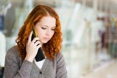 Mädchen, das durch das Telefon spricht. Stockfotografie