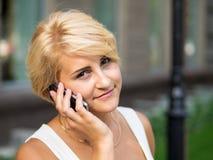 Mädchen, das durch das Telefon spricht Stockfotos