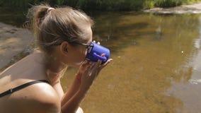 Mädchen, das durch das Wasser mit einer Schale sitzt stock footage