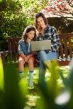 Mädchen, das durch die Mutter verwendet Laptop auf Holzbank sitzt Stockbild