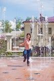 Mädchen, das durch die Wasserstrahlen in einem Brunnen läuft Lizenzfreies Stockfoto