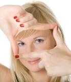 Mädchen, das durch ein Feld gebildet durch ihre Finger schaut Lizenzfreie Stockfotografie