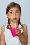 Mädchen, das durch ein Stroh trinkt Lizenzfreie Stockfotos