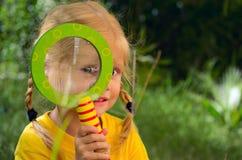 Mädchen, das durch ein Vergrößerungsglas schaut stockfotografie